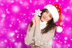 圣诞老人帽子画象的女孩与摆在桃红色颜色背景,圣诞节假日概念,愉快的大雪花玩具和情感 图库摄影