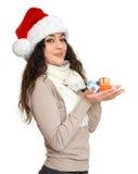 圣诞老人帽子画象的女孩与摆在白色背景,圣诞节假日概念,愉快的极少数一点礼物盒和emot 库存照片