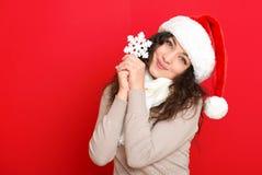 圣诞老人帽子画象的女孩与摆在红颜色背景,圣诞节假日概念,愉快的大雪花玩具和情感 图库摄影