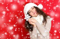 圣诞老人帽子画象的女孩与摆在红颜色背景,圣诞节假日概念,愉快的大雪花玩具和情感 库存照片