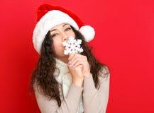 圣诞老人帽子画象的女孩与摆在红颜色背景,圣诞节假日概念,愉快的大雪花玩具和情感 免版税库存图片