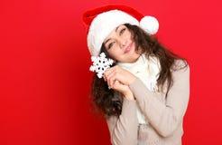 圣诞老人帽子画象的女孩与摆在红颜色背景,圣诞节假日概念,愉快的大雪花玩具和情感 库存图片