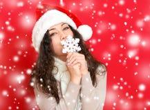 圣诞老人帽子画象的女孩与摆在红颜色背景,圣诞节假日概念,愉快的大雪花玩具和情感 免版税库存照片