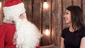 圣诞老人快乐地谈话与黑礼服的一个相当年轻浅黑肤色的男人 库存照片
