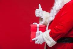 圣诞老人手套的手圣诞节照片有红色giftbox的 背景黑色查出的赞许 库存图片