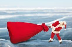 圣诞老人拉扯大红色袋子户外 免版税库存照片