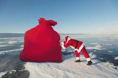 圣诞老人拉扯大红色袋子户外 免版税图库摄影