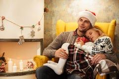 圣诞老人拿着他睡觉daught的` s帽子的快乐的年轻父亲 库存照片