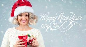 圣诞老人拿着咖啡的` s帽子的妇女 新年好 库存图片