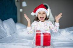 圣诞老人拿着礼物的` s帽子的惊奇的小女孩,当坐与盘的腿在早晨床上时 免版税库存照片