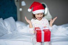 圣诞老人拿着礼物的` s帽子的惊奇的小女孩,当坐与盘的腿在早晨床上时 免版税库存图片