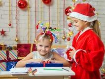 圣诞老人提出了一个愉快的女孩的礼物有烟花的在头 库存图片