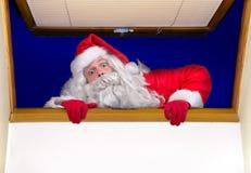 圣诞老人攀登一个开窗口 图库摄影