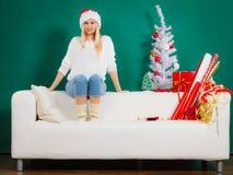 圣诞老人放松在沙发的圣诞节妇女 库存照片
