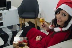 圣诞老人放松在沙发的圣诞节妇女 免版税库存图片
