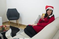 圣诞老人放松在沙发的圣诞节妇女 免版税图库摄影