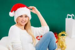圣诞老人放松在沙发的圣诞节妇女 免版税库存照片