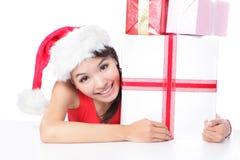 圣诞老人显示xmas礼品的帽子微笑的妇女 免版税库存照片