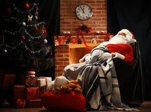 圣诞老人有休息在一把舒适的椅子 免版税库存图片