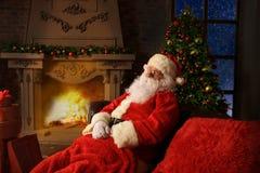 圣诞老人有其它在一把方便的椅子在壁炉附近在家 图库摄影