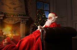 圣诞老人有其它在一把方便的椅子在壁炉附近在家 库存图片