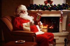 圣诞老人有其它在一把方便的椅子在壁炉附近在家 免版税库存图片
