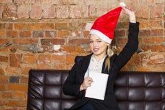 圣诞老人有笔记本和膝上型计算机的女孩女实业家在皮革长沙发的顶楼办公室在衣服 到达天空的企业概念金黄回归键所有权 免版税库存照片