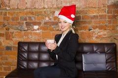 圣诞老人有笔记本和膝上型计算机的女孩女实业家在皮革长沙发的顶楼办公室在衣服 到达天空的企业概念金黄回归键所有权 图库摄影