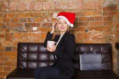 圣诞老人有笔记本和膝上型计算机的女孩女实业家在皮革长沙发的顶楼办公室在衣服 到达天空的企业概念金黄回归键所有权 免版税库存图片
