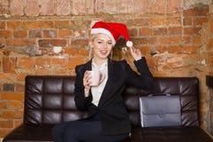 圣诞老人有笔记本和膝上型计算机的女孩女实业家在皮革长沙发的顶楼办公室在衣服 到达天空的企业概念金黄回归键所有权 库存图片