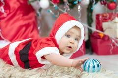 圣诞老人服装的一点圣诞节婴孩 拿着蓝色球的孩子在假日附近点燃背景 图库摄影