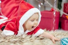 圣诞老人服装的一点圣诞节婴孩 拿着蓝色球的孩子在假日附近点燃背景 免版税库存图片