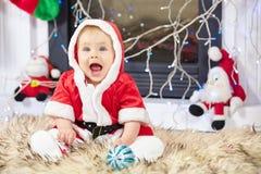 圣诞老人服装的一点圣诞节婴孩 拿着蓝色球的孩子在假日附近点燃背景 免版税库存照片