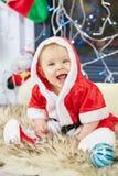 圣诞老人服装的一点圣诞节婴孩 拿着蓝色球的孩子在假日附近点燃背景 库存照片