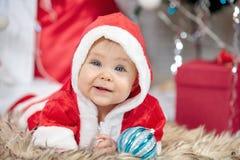 圣诞老人服装的一点圣诞节婴孩 拿着蓝色球的孩子在假日附近点燃背景 库存图片