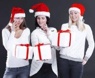 圣诞老人服装的三个少妇有圣诞节的购物 免版税图库摄影