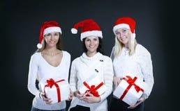 圣诞老人服装的三个少妇有圣诞节shopp的 库存照片