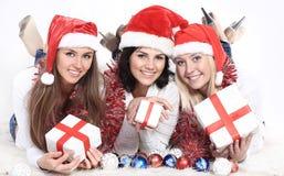 圣诞老人服装的三个愉快的少妇有圣诞节礼物的 免版税库存照片