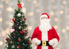 圣诞老人服装的人有圣诞树的 库存图片