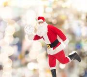 圣诞老人服装的人有时钟的 免版税库存图片