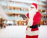 圣诞老人服装的人有片剂个人计算机的 库存照片