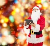圣诞老人服装的人有片剂个人计算机的 库存图片
