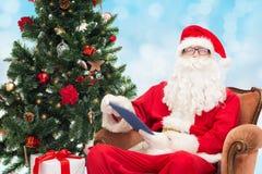 圣诞老人服装的人有片剂个人计算机的 图库摄影
