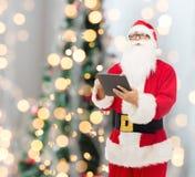 圣诞老人服装的人有片剂个人计算机的 免版税库存图片