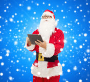 圣诞老人服装的人有片剂个人计算机的 免版税图库摄影