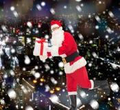 圣诞老人服装的人有礼物盒的 免版税库存图片