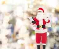 圣诞老人服装的人有笔记薄和袋子的 免版税库存图片