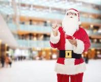 圣诞老人服装的人有笔记薄的 免版税库存照片