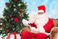 圣诞老人服装的人有笔记薄的 免版税库存图片