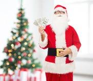 圣诞老人服装的人有美元金钱的 免版税库存照片